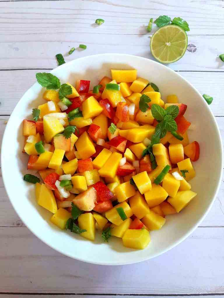 Bright yellow mangoes, red juicy peaches and fresh herbs tossed together to make Mango Peach Salsa that is served in white bowl