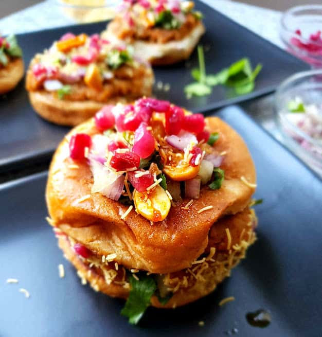Dabeli, the popular Indian street food served on black plate with garnishes.