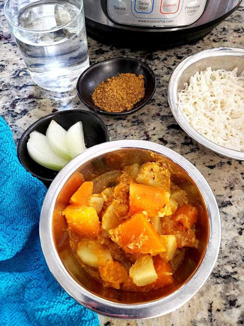 Pumpkin Potato Curry served along with basmati rice, cut onion and chutney. This scruptious curry is easy to make in Instantpot.