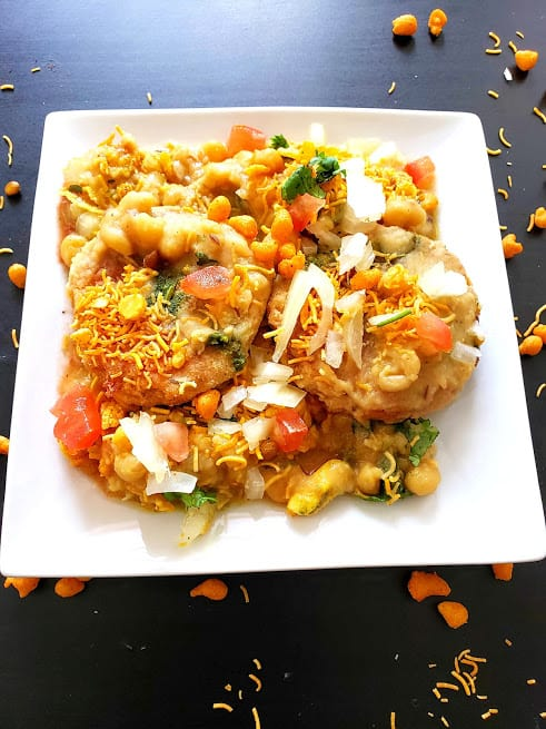 Ragda Pattice served on white platter with bacl backdrop.