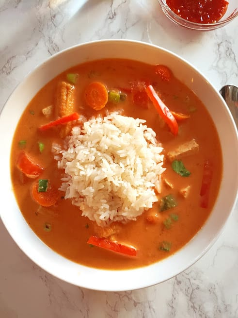 vegetables and tofy thai red curry with dollap of jasmine rice in the middle.