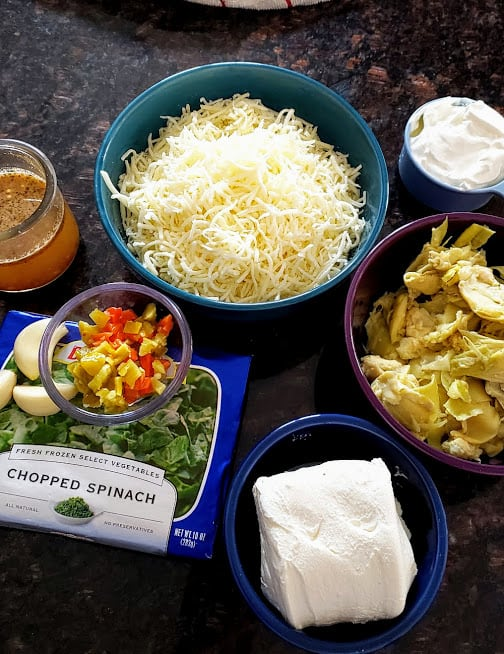 All the ingredients needed to make Cheesy Spinach Artichoke Dip displayed on the countertop.