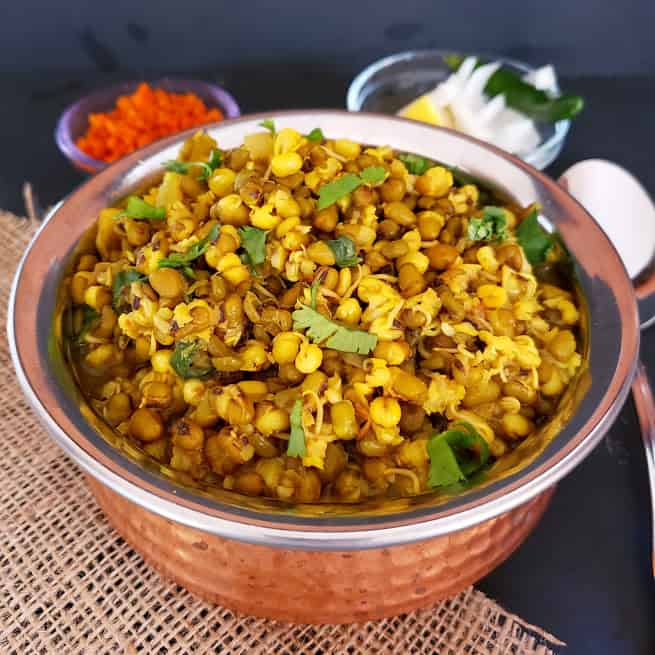 Moong Sprouts Curry cooked perfectly in pressure cooker. Showing close up image of the curry served in ethnic copper container.