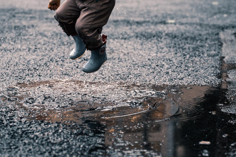 水たまりへ長靴をはいた子供がジャンプしている瞬間