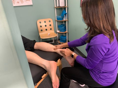 A PTA performs targeted manual therapy on the lower calf and ankle area of a PPTP patient.
