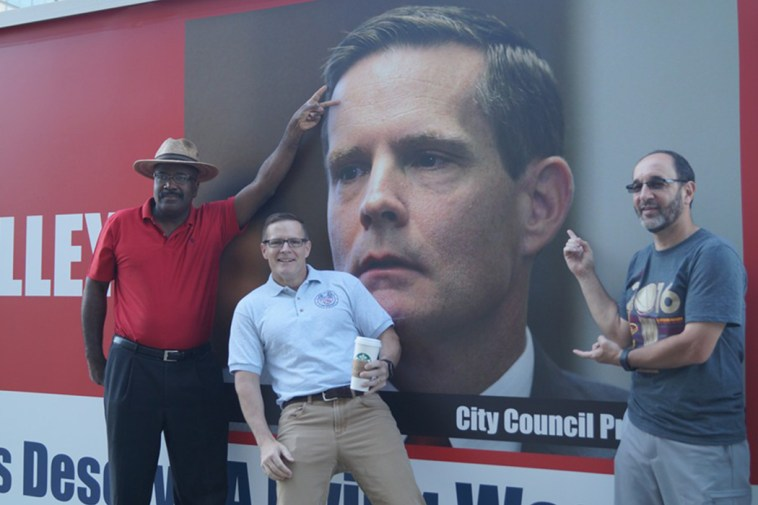 """Cleveland City Councilmen Kevin Conwell, Kevin Kelley and Anthony Brancatelli pose in front of a sign that reads """"Fire Kevin Kelley!"""""""