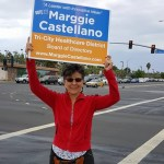 Marggie Castellano holds a sign while campaigning for Tri-City Healthcare District Board of Directors.