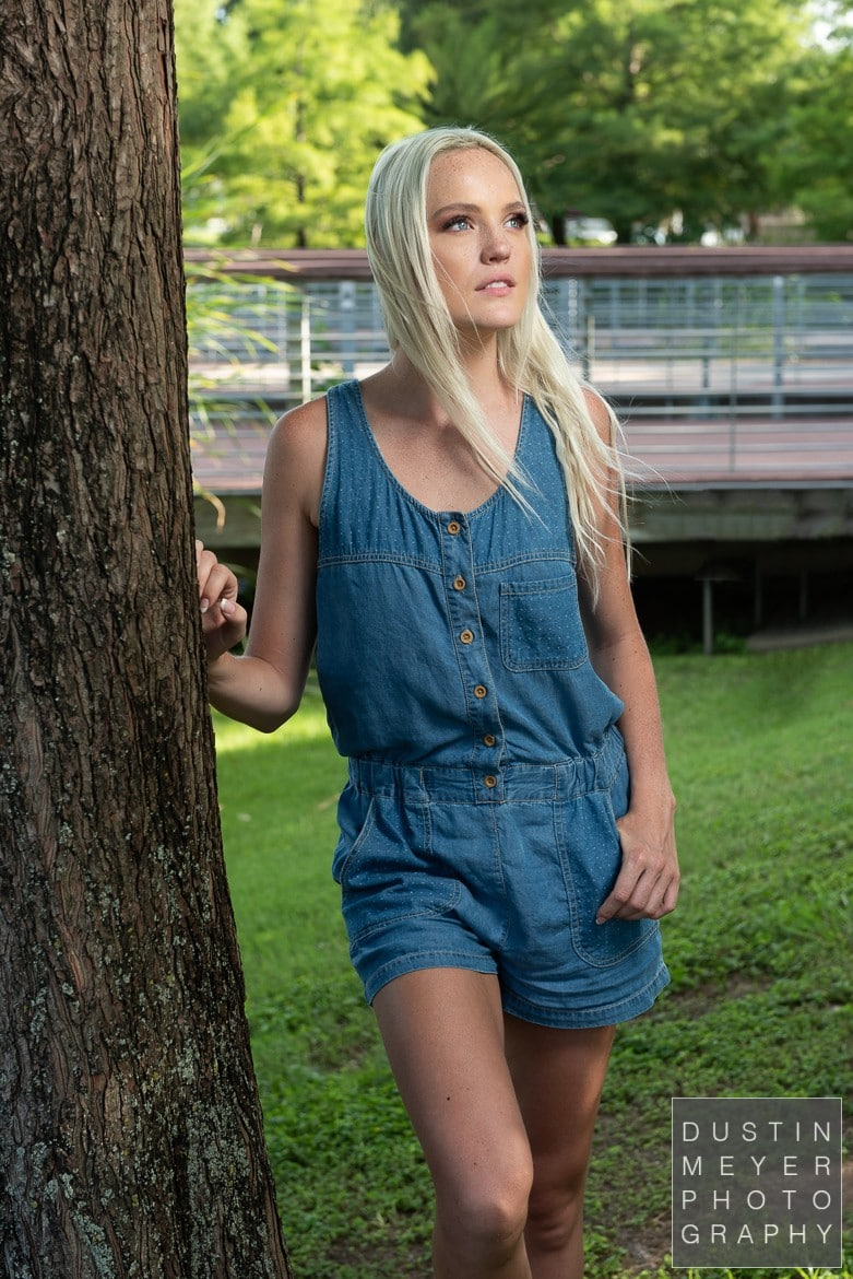 a model headshot of a female with blonde hair and a denim romper taken outdoors