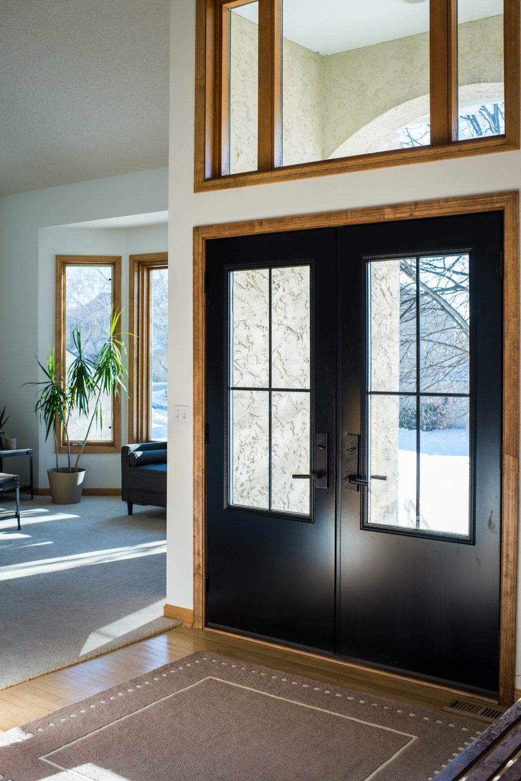 two large black front doors with emtek modern hardware, square rug at the foot of the door