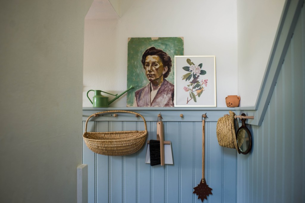 photo of mudroom with items hanging on knobs and 2 art photos resting on shelf