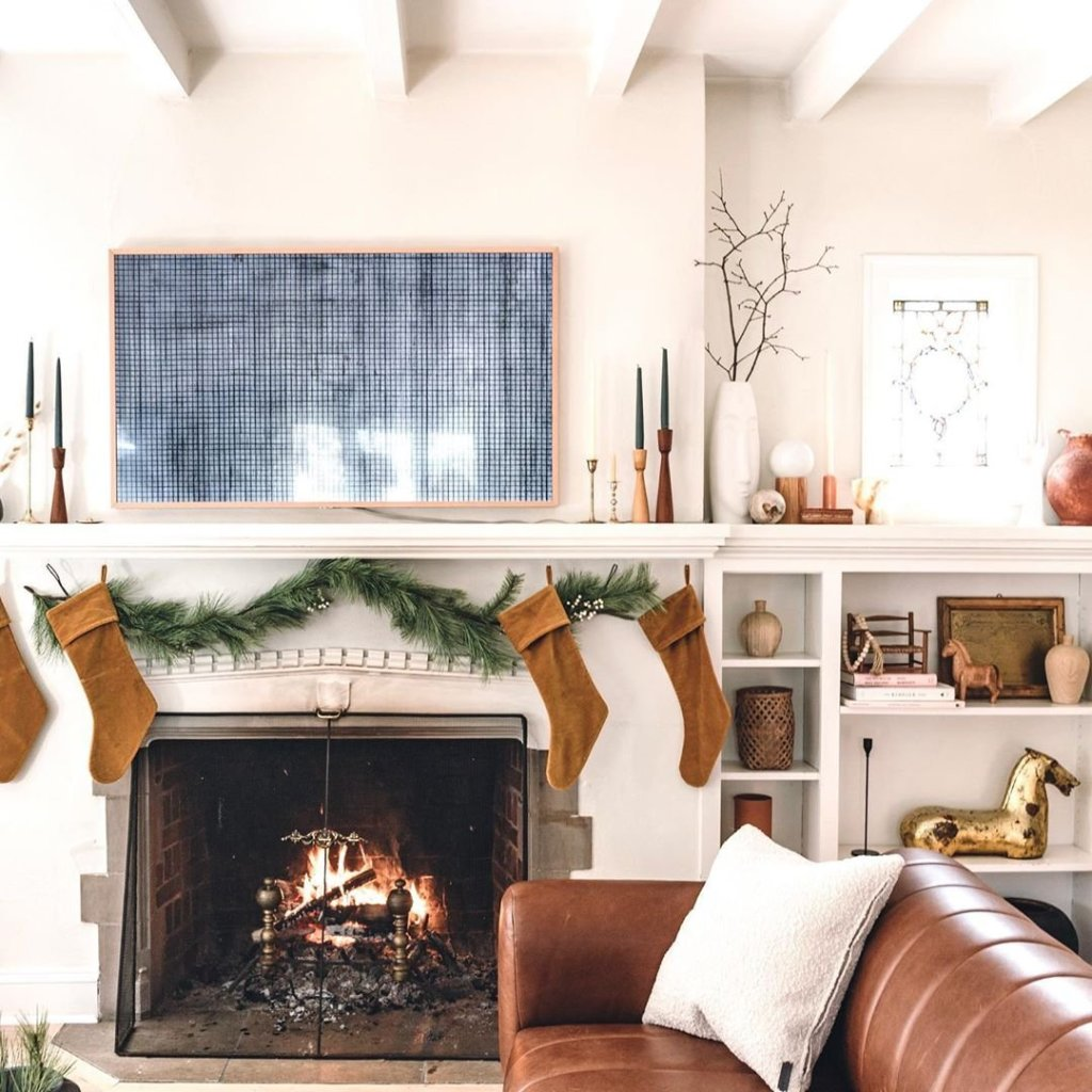 fireplace with holiday decor, large photo above fireplace that has stockings and sofa