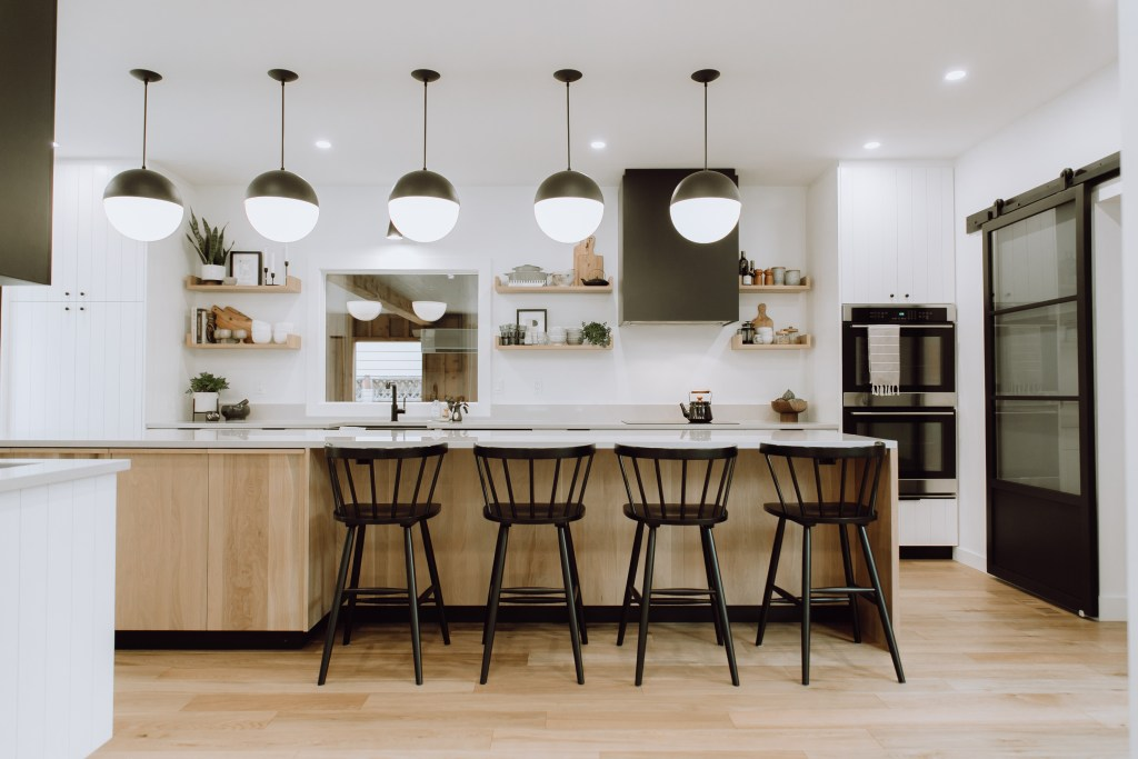 Matte black finishes, white countertops and cabinetry paired with a wood island and floors.