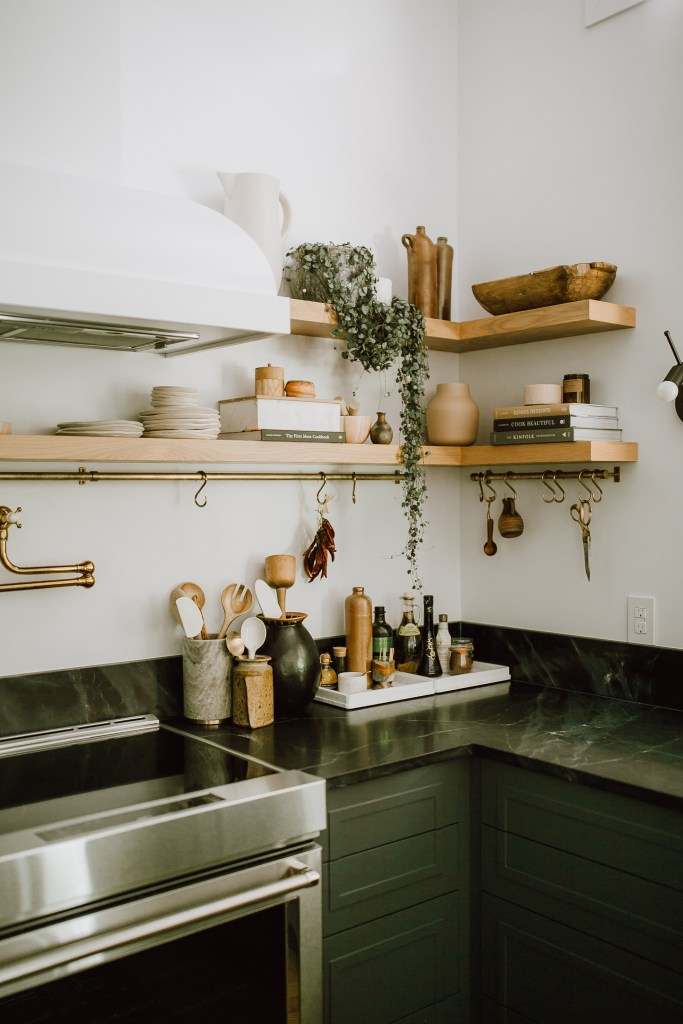 Open shelving with live plants, cookbooks and wood accessories are showcased in this photo above the countertops.