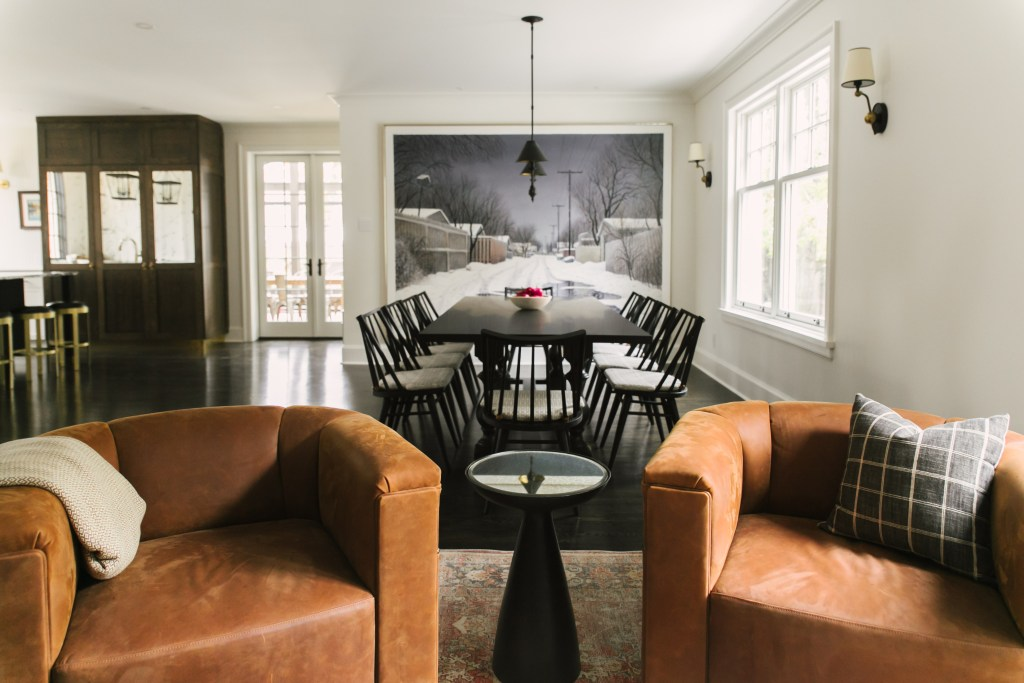 A view into the dining room with 8 chairs and a large painting resting on the wall behind the dining room table.
