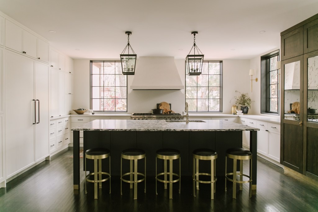 three windows allow natural light into the kitchen with brass, white cabinets and dark tones in the island base.