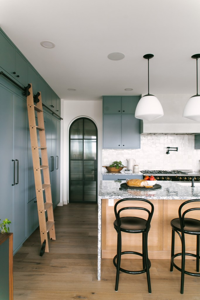 Blue-green kitchen cabinetry, milk glass pendants in an open kitchen with an island and arched doorway.