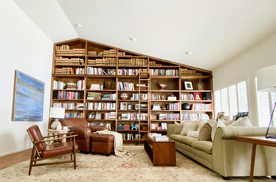 A custom floor to ceiling bookshelf was made to fit the modern desert home.