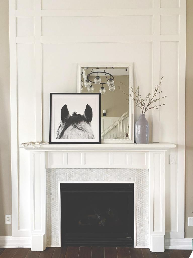 Updated fireplace with white wood trim floor to ceiling and penny tiles surrounding the fireplace opening.