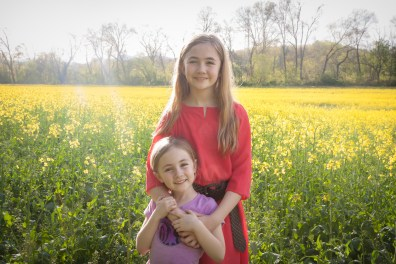 Two girls stand in a field of yellow flowers near the Biltmore in Asheville, NC NotSoSAHM