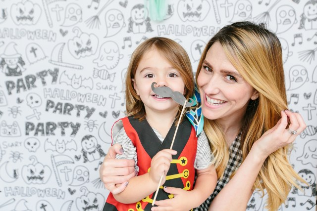 Royale Ziegler and son pose in front of Hallloween photo backdrop