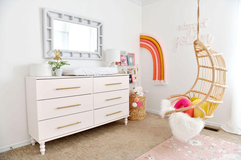 Rainbow kwekerij met hangende rotan stoel en roze IKEA hack dressoir