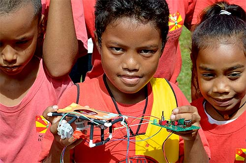 palau student holds circuit board for ROV he made
