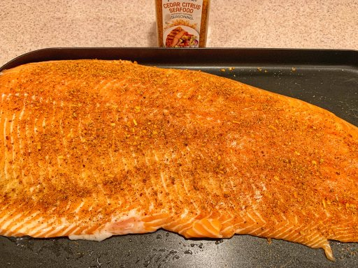 Large salmon filet on a black pan with a bottle of seasoning nearby