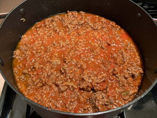 Meat sauce with added red crushed tomatoes in a black chili pot