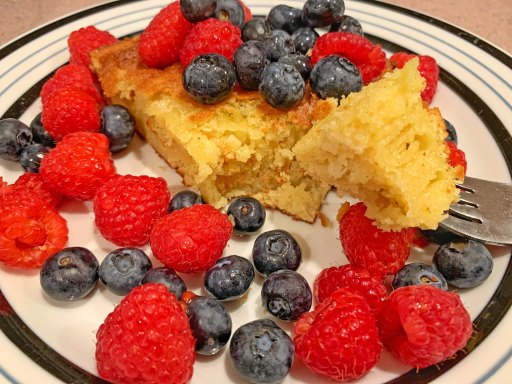 Piece of Vasilopita cake on a plate with blueberries and raspberries