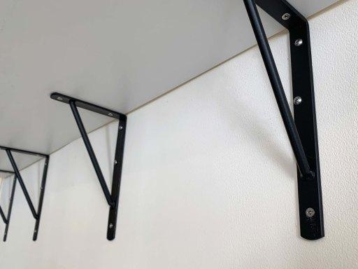 Four garage shelf brackets holding up a garage shelf