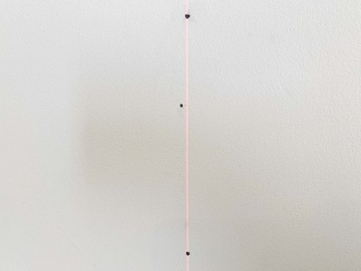 Laser level cross hair running through garage shelf bracket screw holes marked on a wall