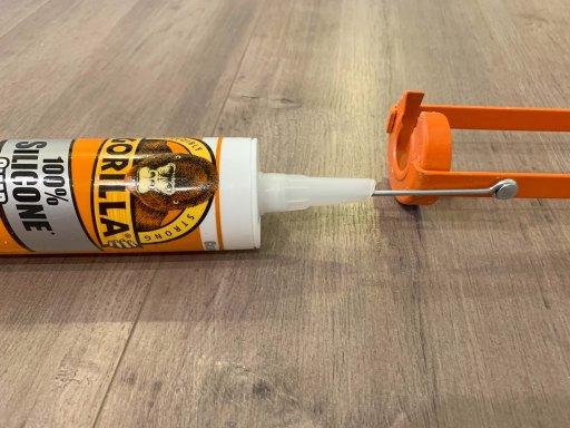 Bottle of caulk being punctured by the seal puncture tool of an orange caulk gun