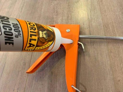 Bottle of caulk inserted into the spout cutter of an orange caulk gun