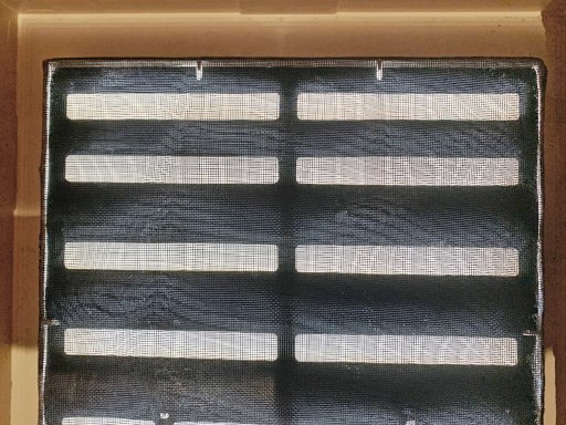 Attic wall louver covered in black mesh