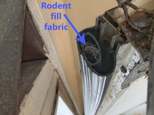 Rodent control fill fabric stuffed into a garage door bottom rubber strip