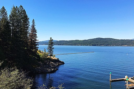View of Lake Coeur d'Alene in Coeur d'Alene, Idaho showing blue water, green trees, and blue skies