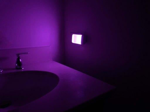Purple night light glowing in a dark bathroom