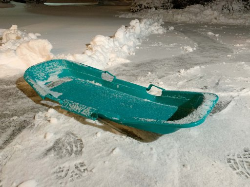 Empty green sled in snow on a driveway