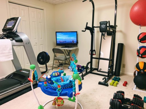 Home gym showing a treadmill, TV, medicine balls, weights, and an activity jumper for a child