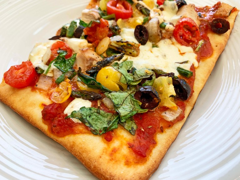 Large slice of grilled chicken and veggie pizza on a white plate