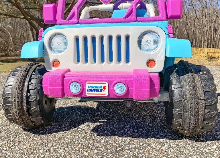 Blue Power Wheels with added tire treads on a driveway.