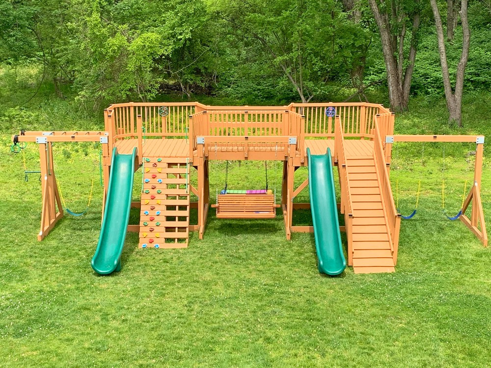 Large playground stained brown with two green slides, swings, and monkey bars