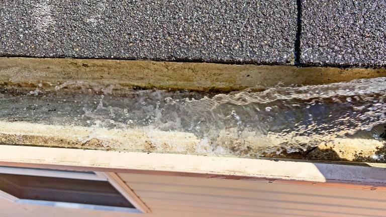Hose water flushing debris from a gutter
