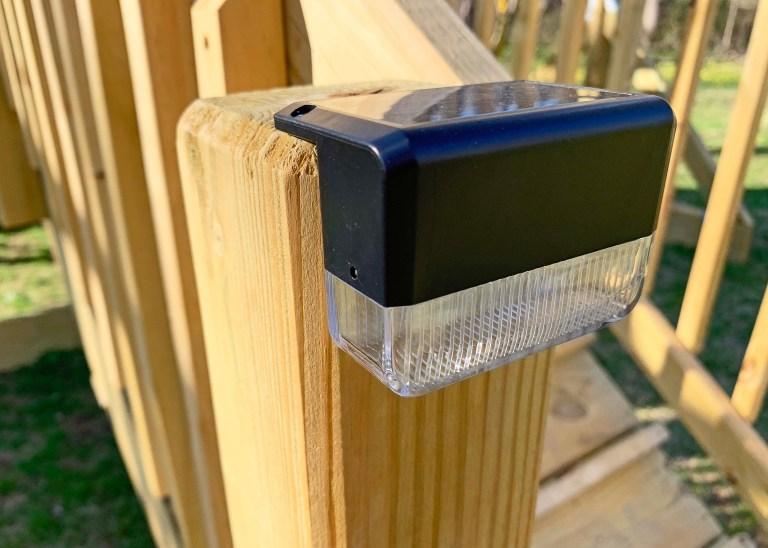 Solar deck lights on a playground railing post