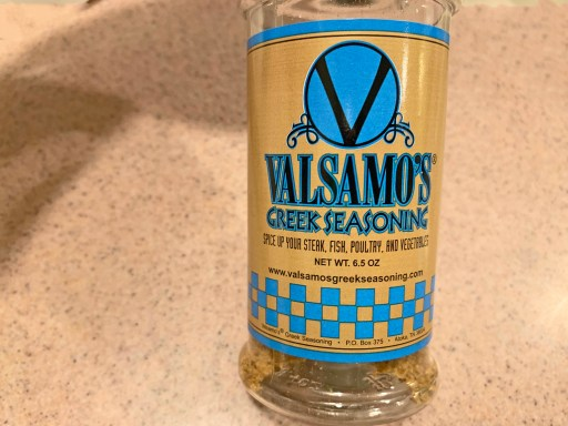Bottle of fish seasoning with black lettering and blue colors