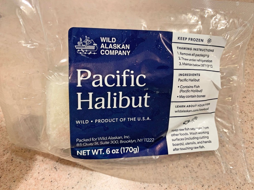 Frozen fillet of white fish that is in a vacuum-sealed bag with white lettering on a blue background