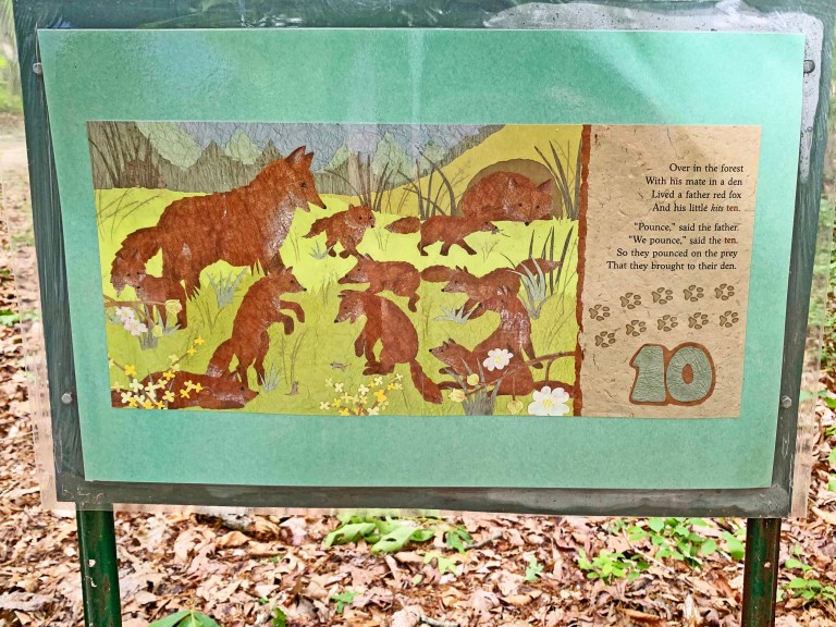Green sign with the number ten and ten foxes