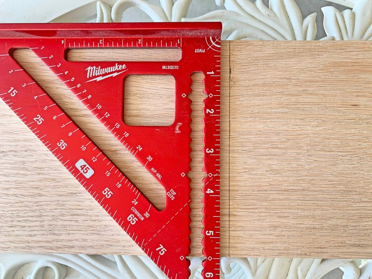 Red carpentry/rafter triangleon top of a piece of light-colored wood