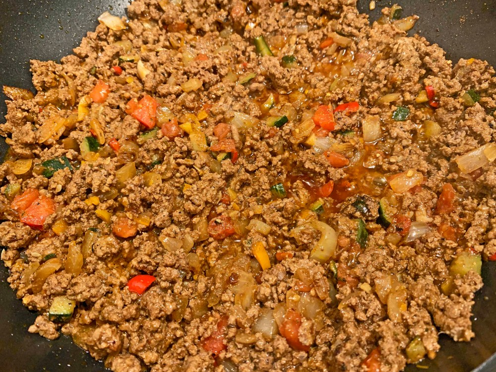 Brown ground beef with assorted colorful vegetables that have been cooked in a black frying pan