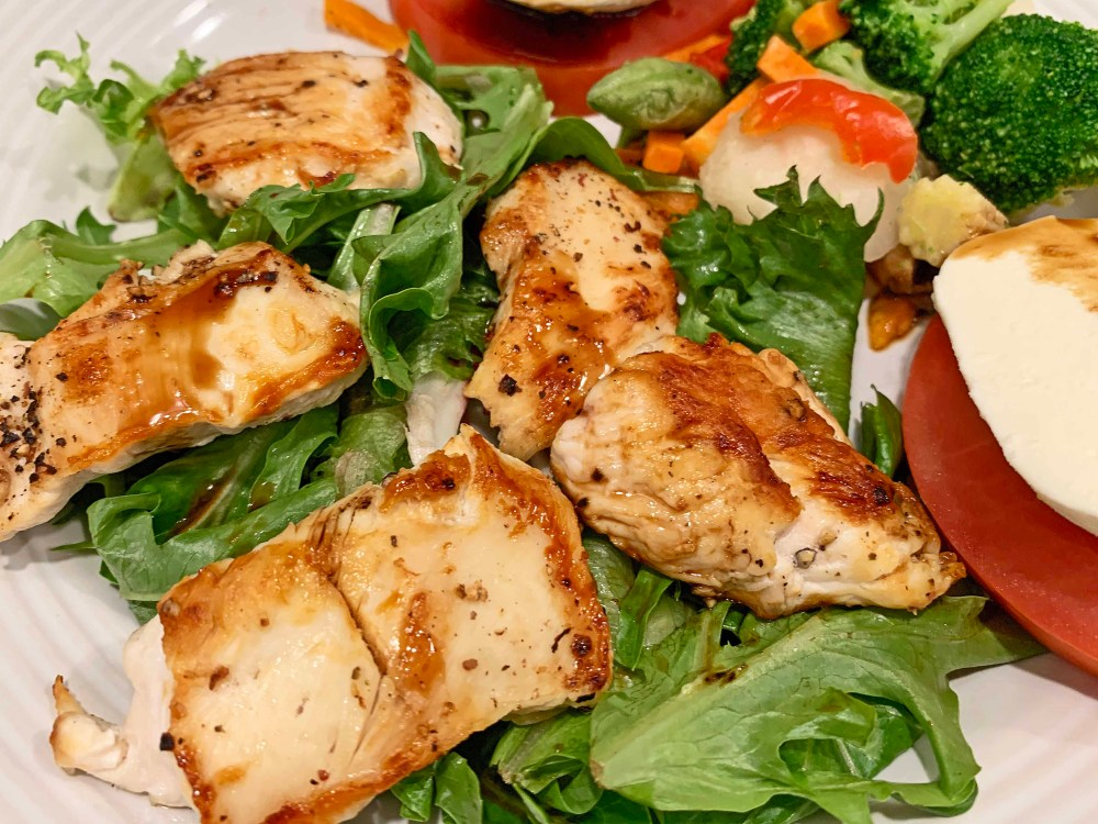 Cooked chicken on green salad with red tomatoes and white mozzarella cheese